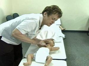A woman learns CPR techniques to treat children.