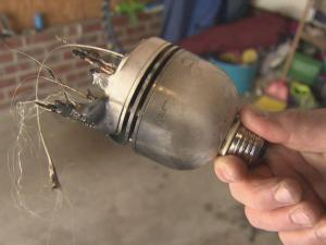 Jim Guettler holds the remnants of his burnt-out compact fluorescent lightbulb.