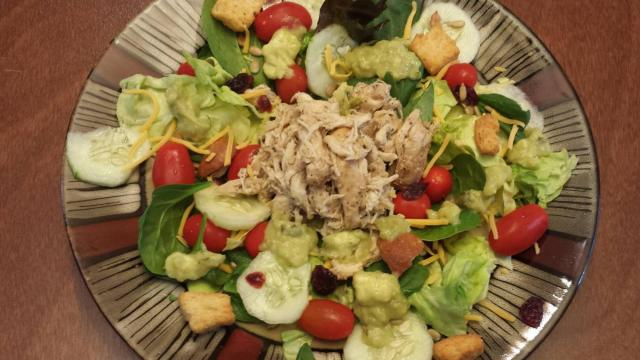 Shredded chicken on salad with avocado salsa dressing