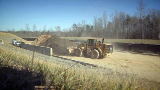 A front-end loader scoops up coal ash from the Dan River Steam Station in Eden on Jan. 14, 2016, and dumps it into a rail car to be hauled to a landfill in Virginia.