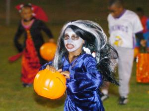 Latia Clayton runs to collect candy-filled eggs during a Halloween Egg Hunt in Oxford, Miss. (AP Photo/Oxford Eagle, Bruce Newman)