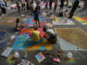 Friends Greyson Smith, Jessica Denis, Ashleigh Short, and Brianne Johnson work on their chalk artwork for donations on Martin Street near Moore Square.
