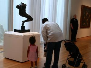 A father shows his children a statue by Auguste Rodin.