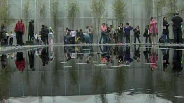 Visitors to the North Carolina Museum of Art are doubled up by a reflecting pool.