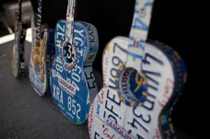 License-plate guitars created by Peter Geiger, of Cary, lean on a table during Artsplosure Saturday morning. (Photo credit: Matt Moore)