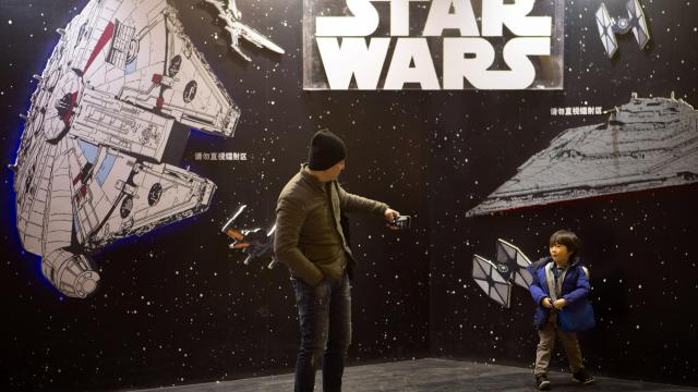 """A man takes a smartphone photo of his son at a """"Star Wars"""" promotional display at a shopping mall in Beijing, Saturday, Jan. 9, 2016. The record-breaking """"Star Wars"""" opened Saturday in China, where it is far from certain to draw in enough moviegoers to knock off """"Avatar"""" as the world's all-time biggest grossing movie. (AP Photo/Mark Schiefelbein)"""