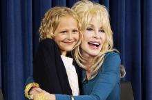 "Young Alyvia Alyn Lind gets a hug from Dolly Parton as they publicize the TV movie ""Dolly Parton's Coat of Many Colors,"" now on DVD. The girl plays Parton as an 9-year-old in the film. (Deseret Photo)"