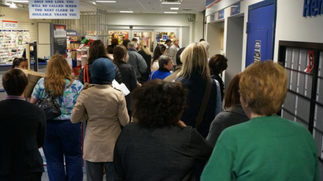 Dozens wait in line at the U.S. Post Office on East Six Forks Road in Raleigh on Dec. 16, 2013. The postal service expected to process 610 million pieces of mail nationwide, about 80 million more letters and packages than the average day. (Photo by Edward Wilson)