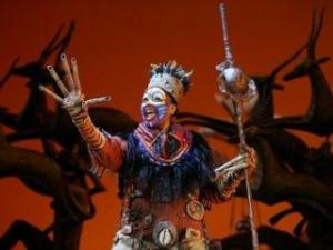 """Phindile Mkhize as """"Rafiki"""" in the opening number """"The Circle of Life"""" from THE LION KING National Tour.  sney.  Photo Credit:  Joan Marcus."""