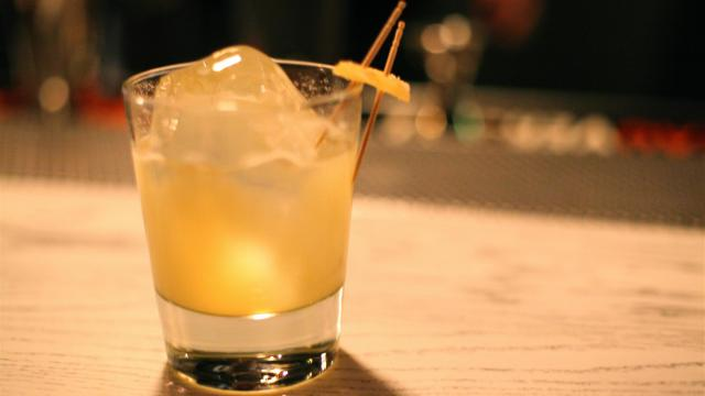 """Fox Liquor Bar's Penicillin, built with a blended scotch whiskey, honey, fresh lemon, ginger, topped with a few eyedrops of single malt Islay Scotch Whisky, served """"on the rock"""" and garnished with a candied ginger."""