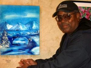 """Public Works employee Donald Baldwin poses with his entry """"Blue Ice."""" He entered the amateur painting category in 2010 competition. (Image from the National Arts Program)"""
