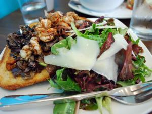 A fresh green salad balances the bitter, salty, peppery richness of bruschetta topped with North Carolina shrimp, radicchio, pancetta and balsamic glaze at Toast in downtown Durham.