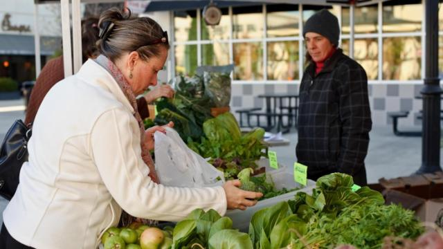 Customers shop for fresh produce at the Wild Onion Farms booth during the Midtown Farmers Market at North Hills in Raleigh on November 17, 2012.