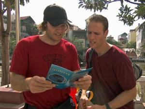 "Bates and Anthony Battaglia read a clue on ""The Amazing Race."" (CBS photo)"