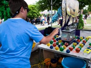 Harrison Ray, 14, of Fayetteville, tosses Ping-Pong balls into colorful, water filled bowls at the Fayetteville Dogwood Festival on April 27, 2013. Ray made five Ping-Pong balls into the bowls, which won him five goldfish. Photo by John West