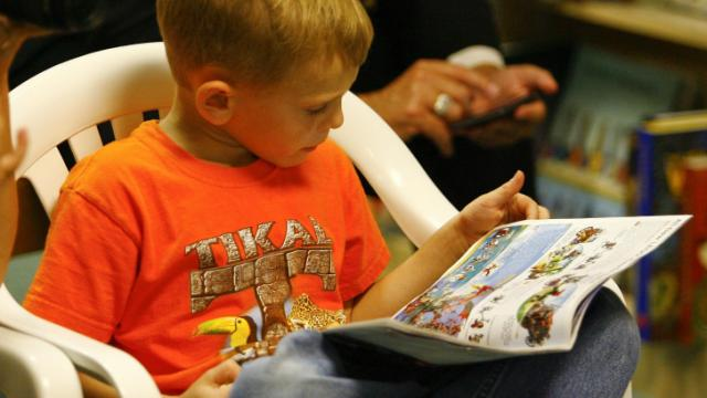 A little boy reads a book during 'Weird Al' Yankovic book singing of My New Teacher and Me at Quail Ridge Books & Music in Raleigh Friday afternoon.  Al is currently on his book signing tour throughout the US (photo by Wes Hight).