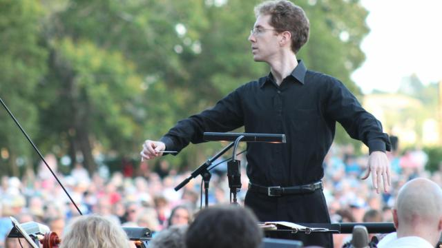 Symphony Associate Conductor David Glover conducts an outdoor concert.