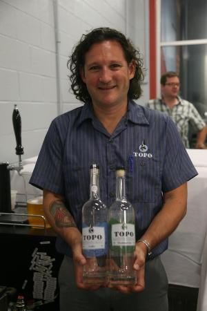 Top of the Hill distillery tour and fundraiser for the Rape Crisis Center. Esteban McMahan shoes of the TOPO bottles