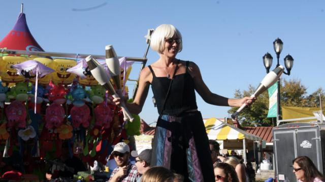 A woman on stilts stands high above the crowd at the North Carolina State Fair on Sunday, Oct. 21, 2012.