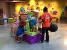 "At a special members-only event, kids at Marbles Kids Museum stack up presents to be knocked down with a giant ""wrecking ball."""