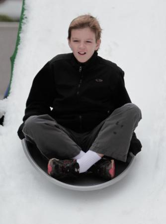 A boy sleds down the hill Sunday afternoon at City Plaza in downtown Raleigh. (Photo by Wes Hight)