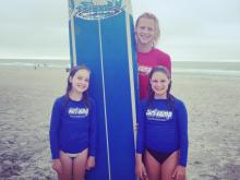 Amanda's daughter and niece with their instructor at surf camp.