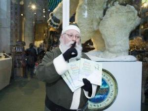 """This undated handout photo provided by Plan G shows the Green Santa holding copies of the book """"When Santa Turned Green,"""" by Victoria Perla at FAO Schwarz in New York, Friday, Nov. 16, 2007. (AP Photo/Plan G, Mark Hartman)"""