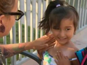 Cristina Riley helps her daughter apply sunscreen.