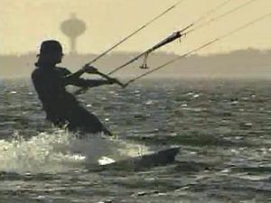 A kiteboarder zips along the surface of the Atlantic Ocean, off Buxton in the Outer Banks.
