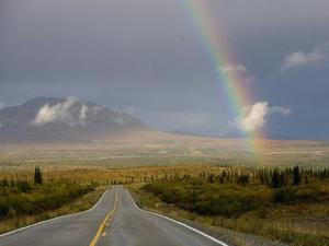 A rainbow rests over the Alaskan pipeline as the Denali Highway stretches forward.