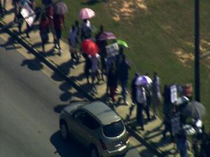 Students lined Fayetteville Road in Durham Friday afternoon in protest of planned school budget cuts.