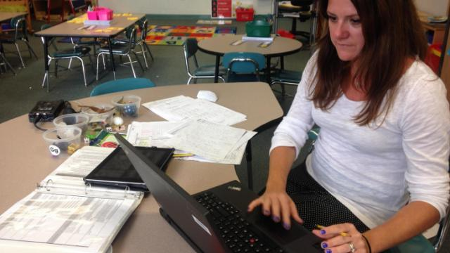 Kindergarten teacher Michelle Russolese records her student observations into a program that is part of the K-3 formative assessment process. (Photo by Reema Khrais / WUNC)