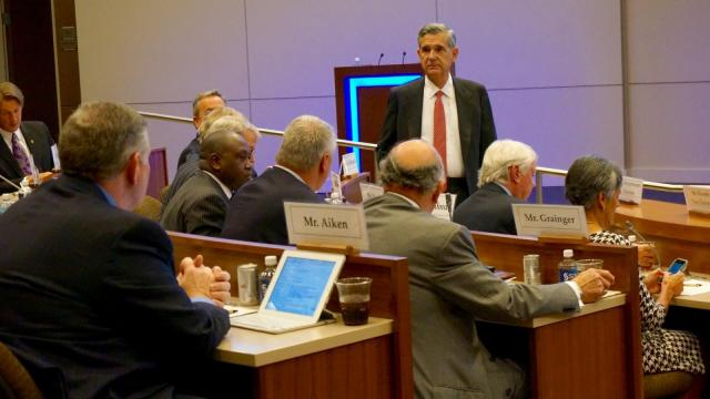 John C. Fennebresque (standing), chairman of the University of North Carolina System Board of Governors, waits while the board assembles in person and over the phone for an emergency meeting Oct. 16, 2015.