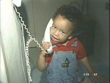 Gage Cheatem, 2, demonstrates how he dialed 911 when his mother passed out Thursday afternoon. (WRAL-TV5)