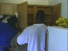 Workers install new cabinets inside the Oxford Manor housing project