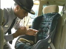 Trooper D.P. Tofoya finds a broken bracket on this car seat.