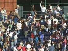 A happy fan holds up a fly ball that was popped into the stands by a Durham Bull.