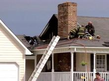 Firefighters work on the roof of a Garner house to ensure the blaze is out.(WRAL-TV5 News)