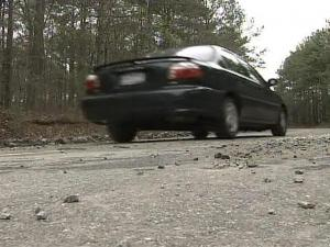 Holly Springs says heavy trucks like those that would come top a widely opposed landfill have broken the surface of a nearby road.