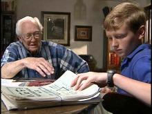 James Creech, 82, and Chase Shermer, 13, look through Creech's World War II documents. The young student is fighting to get his neighbor's war records corrected.