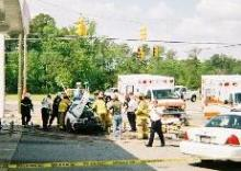 Firefighters work to extricate a Rock Mount police officer from his cruiser on Sunday, April 29, 2007, following a crash at an intersection in the city. (Douglas Barfield photo)