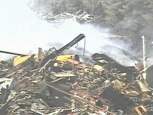 A fire at a Smithfield scrap metal yard continued to smolder Tuesday.
