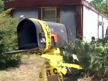 Crime scene tap still hangs on the mailbox outside George Davis' Henderson home Friday afternoon.