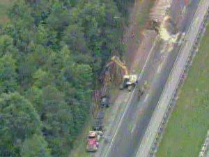 A tractor-trailer carrying a load of logs overturned on northbound I-95 in Halifax County, shutting down both lanes.
