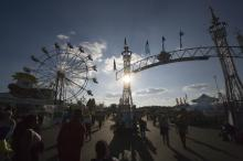 Fairgoers mingle around the entrance to the Raleigh Fairgrounds as the late afternoon sun begins to set.