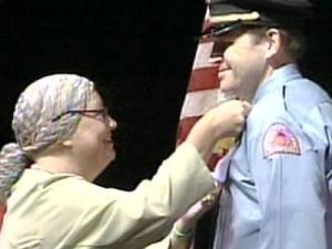 Marian Dolan, the sister of Raleigh police Chief Harry Dolan pins a badge to her brother's uniform Tuesday, Sept. 18, 2007, during his swearing-in ceremony.
