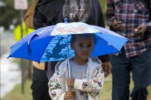 Jay-Quan Nixon, 2, walks along Lenoir street with her umbrella after a brief but heavy rain fell on Raleigh Thursday morning.