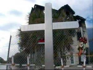 A metal cross and several smaller crosses stand in front of the charred remnants of the Ocean Isle Beach house where seven South Carolina college students died Oct. 28, 2007.