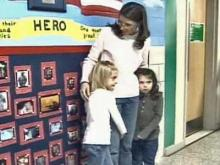 Wesley Bauguess and her two daughters, Ryann, 7, and Ellie, 5, at the opening of a mural at their school dedicated to their father, Maj. Larry Bauguess, who died in combat in Pakistan.