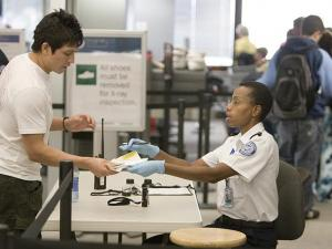 A TSA employee inspects a traveler's boarding pass and identification before he is allowed through to security.